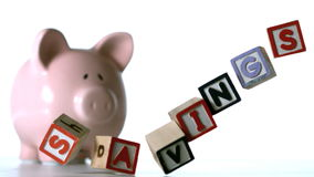 Blocks spelling savings dropping down in front of a pink piggy bank. In slow motion stock video