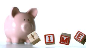Blocks spelling time falling over beside a piggy bank Stock Photography