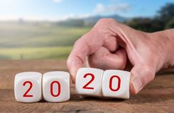Blocks spelling 2020 on wooden table with sunlit landscape in background stock photography