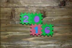 Blockschrift und Nr. 2016 mit hölzernem Hintergrund Stockbild