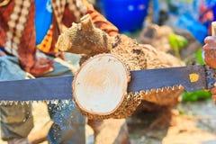 Blockwindenmann schneidet Holz Stockfotografie