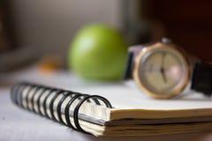 Blocnote en klok op de lijst Royalty-vrije Stock Afbeeldingen