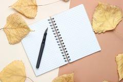 Blocnote en pen op een beige achtergrond met gevallen bladeren Oktober-tijd, de herfstinspiratie, journalistiek, hoogste mening stock foto