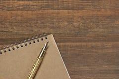 Blocnote met de Gouden Lijst van Fonteinpen on the old wood Stock Foto