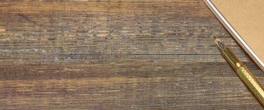 Blocnote met de Gouden Lijst van Fonteinpen on the old wood Stock Afbeelding