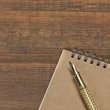 Blocnote met de Gouden Lijst van Fonteinpen on the old wood Royalty-vrije Stock Foto