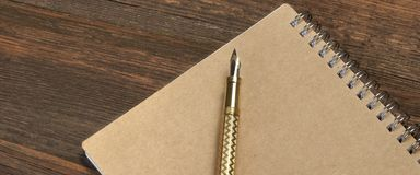 Blocnote met de Gouden Lijst van Fonteinpen on the old wood Royalty-vrije Stock Afbeeldingen