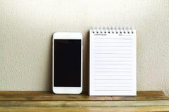 Blocnote met smartphone op hout en muurachtergrond het gebruiken van behang voor onderwijs, bedrijfsfoto Neem nota van het produc Stock Afbeelding