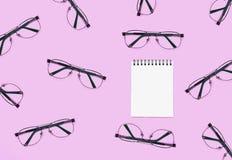 Blocnote met vele glazen op roze lijst Stock Fotografie