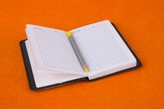 Blocnote op een oranje achtergrond Notitieboekje en potlood School en Onderwijs kantoorbehoeften royalty-vrije stock foto's