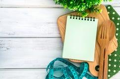 Blocnote op hakbord met houten vork en lepel en de metende band op witte lijst, receptenvoedsel of dieetplan voor gezondheid Stock Fotografie