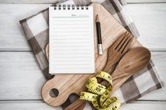 Blocnote op hakbord met houten vork en lepel en measur Royalty-vrije Stock Afbeeldingen