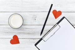Blocnotepotlood twee rood hartendocument met melk Stock Afbeeldingen