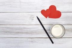 Blocnotepotlood twee rood hartendocument met melk Stock Afbeelding