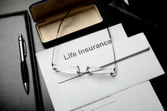 Blocnotes, glazen en levensverzekeringsdocumenten Royalty-vrije Stock Foto