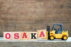 Bloco amarelo A da letra da posse da empilhadeira do brinquedo para terminar a palavra Osaka imagem de stock royalty free