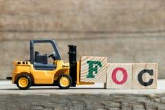 Bloco amarelo F da letra da posse da empilhadeira do brinquedo para terminar a palavra FOC & x28; Abreviatura de gratuitamente &  fotos de stock royalty free
