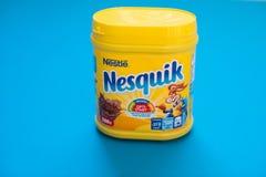 Bloco da bebida Nesquik do chocolate e do cacau por Nestle no fundo azul foto de stock