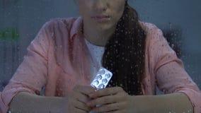 Bloco de bolha guardando fêmea só comprimido dos comprimidos perto da janela chuvosa, doença vídeos de arquivo