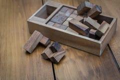 Bloco de madeira Brain Teaser Puzzle no fundo de madeira espalhado para fora Imagens de Stock