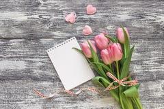 Bloco de notas aberto da placa com tulipas e corações em um backg de madeira cinzento Fotos de Stock Royalty Free