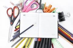 Bloco de notas aberto em materiais de escrit?rio no fundo branco imagem de stock
