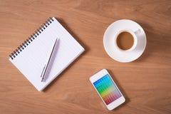 Bloco de notas, amostras de folha da cor e copo de café vazios na tabela de madeira Fotografia de Stock Royalty Free