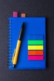 Bloco de notas azul com etiquetas e a pena multi-coloridas Foto de Stock