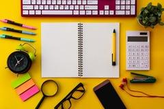 Bloco de notas branco vazio com o escritório e os acessórios pessoais isolados no fundo amarelo fotos de stock royalty free