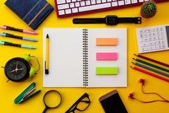 Bloco de notas branco vazio com o escritório e os acessórios pessoais isolados no fundo amarelo foto de stock