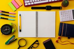 Bloco de notas branco vazio com o escritório e os acessórios pessoais isolados no fundo amarelo imagem de stock