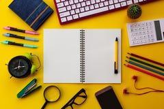 Bloco de notas branco vazio com o escritório e os acessórios pessoais isolados no fundo amarelo foto de stock royalty free