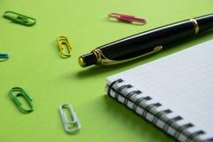 Bloco de notas, clipes de papel e pena no materiais de escritório de superfície verdes, de volta à escola Fotografia de Stock