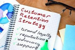 Bloco de notas com estratégias da retenção do cliente das palavras Imagens de Stock Royalty Free