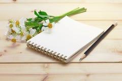 Bloco de notas com a flor do lápis e da grama Imagens de Stock Royalty Free
