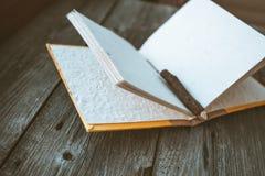 Bloco de notas com o lápis na tabela de madeira (imagem tonificada cor do vintage) Imagem de Stock Royalty Free