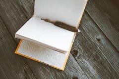 Bloco de notas com o lápis na tabela de madeira (imagem tonificada cor do vintage) Fotografia de Stock Royalty Free