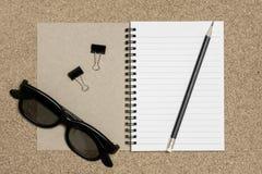 Bloco de notas com o lápis no fundo da placa da cortiça Foto de Stock