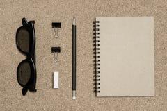 Bloco de notas com o lápis no fundo da placa da cortiça Fotografia de Stock Royalty Free