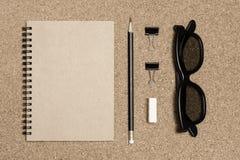 Bloco de notas com o lápis no fundo da placa da cortiça Fotos de Stock