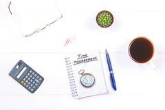 Bloco de notas com o texto: gestão de tempo Tabela branca com calculadora, cacto, papel de nota, caneca de café, pena, vidros e p Foto de Stock