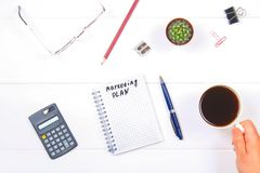Bloco de notas com o texto: plano de marketing Tabela branca com calculadora, cacto, papel de nota, pena, vidros Uma mão guarda u Fotos de Stock Royalty Free
