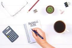 Bloco de notas com o texto: plano de negócios Tabela branca com calculadora, cacto, papel de nota, pena, vidros Uma mão guarda um Imagem de Stock Royalty Free