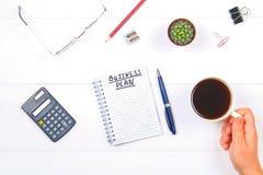 Bloco de notas com o texto: plano de negócios Tabela branca com calculadora, cacto, papel de nota, pena, vidros Uma mão guarda um Fotografia de Stock