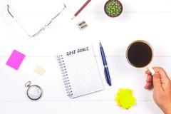 Bloco de notas com o texto: plano de negócios Tabela branca com pulso de disparo, cacto, papel de nota, pena, vidros Uma mão guar Fotografia de Stock