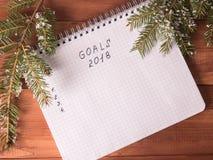Bloco de notas com objetivos e um lápis vermelho em um Year& novo x27; fundo de s Fotos de Stock