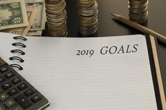 Bloco de notas com 2019 objetivos texto, calculadora, lápis, fundo do dinheiro foto de stock royalty free