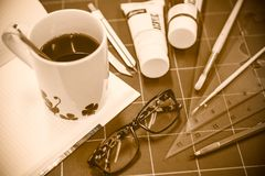 Bloco de notas com objetos estacionários para a arte finala e o café quente Foto de Stock