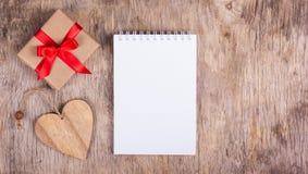 Bloco de notas com página vazia, um coração de madeira e a caixa de presente pequena com uma curva vermelha Fotos de Stock Royalty Free