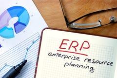 Bloco de notas com sistema de planeamento do recurso da empresa (ERP) na tabela do escritório fotografia de stock royalty free